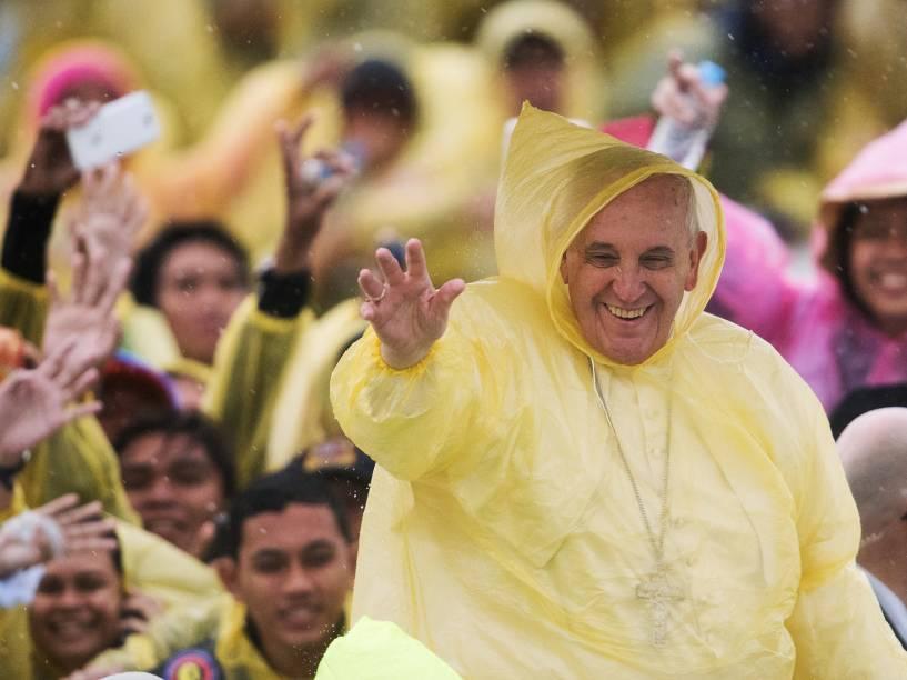 Papa Francisco usa capa de chuva de plástico enquanto acena para fieis na cidade de Tacloban, nas Filipinas