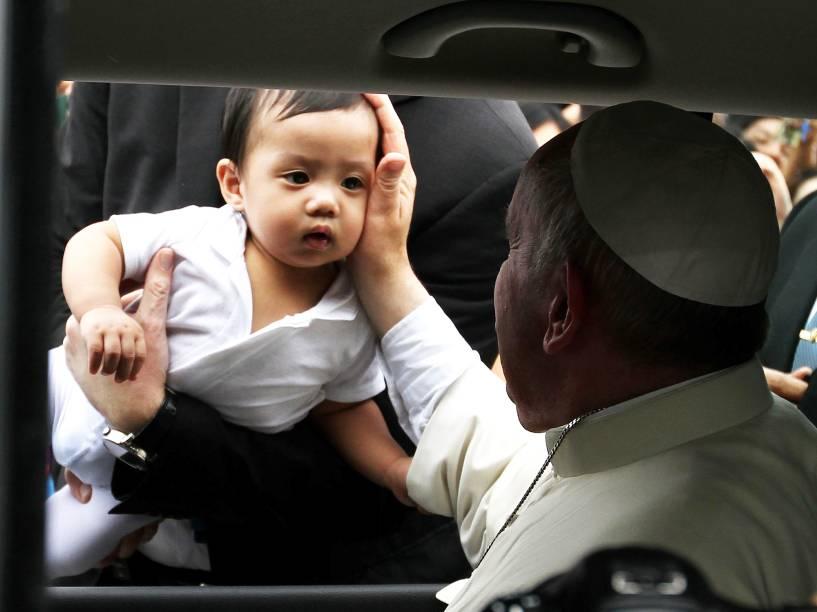 Papa Francisco toca o rosto de um bebê no aeroporto da cidade de Manila, capital das Filipinas - 17/01/2015