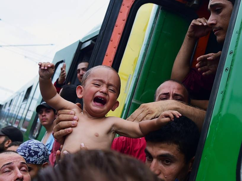 Refugiado segura um menino chorando do lado de fora de um trem que seguia para a fronteira com a Áustria, e foi parado em Bicske, na Hungria - 03/09/2015