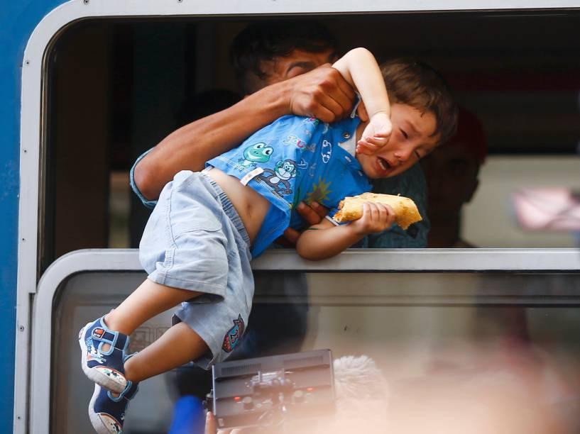 Homem puxa um menino para dentro de um trem através de uma janela na estação de Keleti, em Budapeste, Hungria - 03/09/2015
