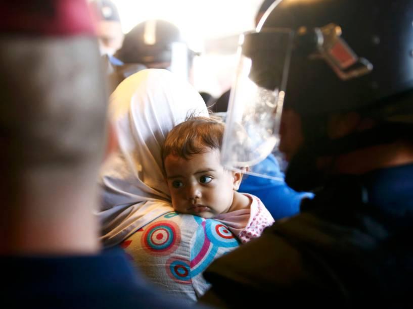 Refugiados caminham através de um bloqueio de policiais após desembarcarem na estação ferroviária de Bicske, Hungria - 04/09/2015