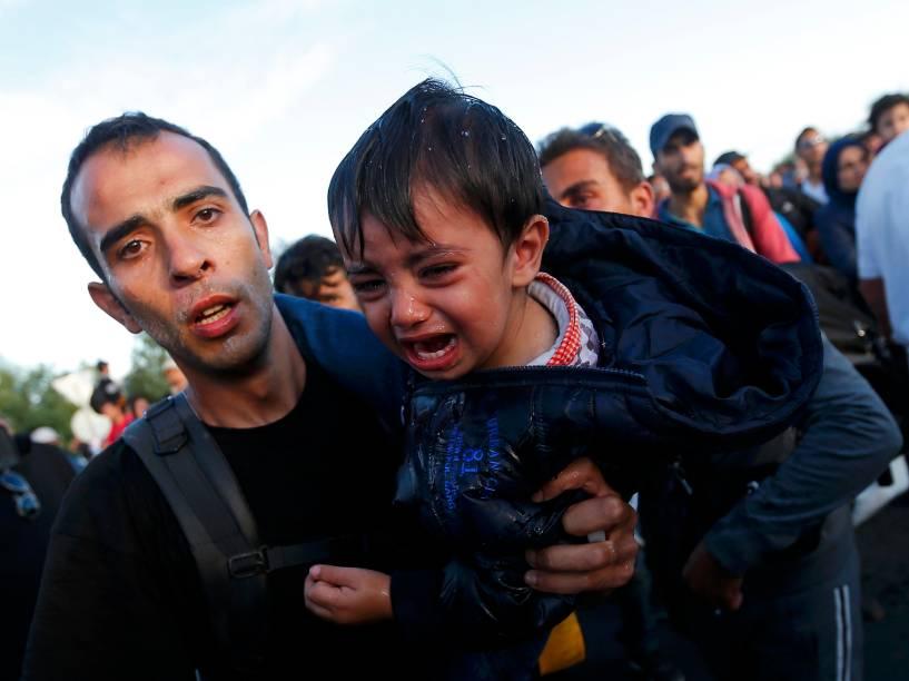 Refugiado segura seu filho em um ponto de coleta na vila de Röszke, Hungria - 07/09/2015