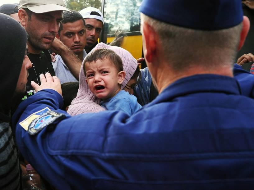 Policial fala com refugiados que cruzaram a fronteira com Sérvia em um ponto nos arredores da cidade húngara de Szeged - 08/09/2015