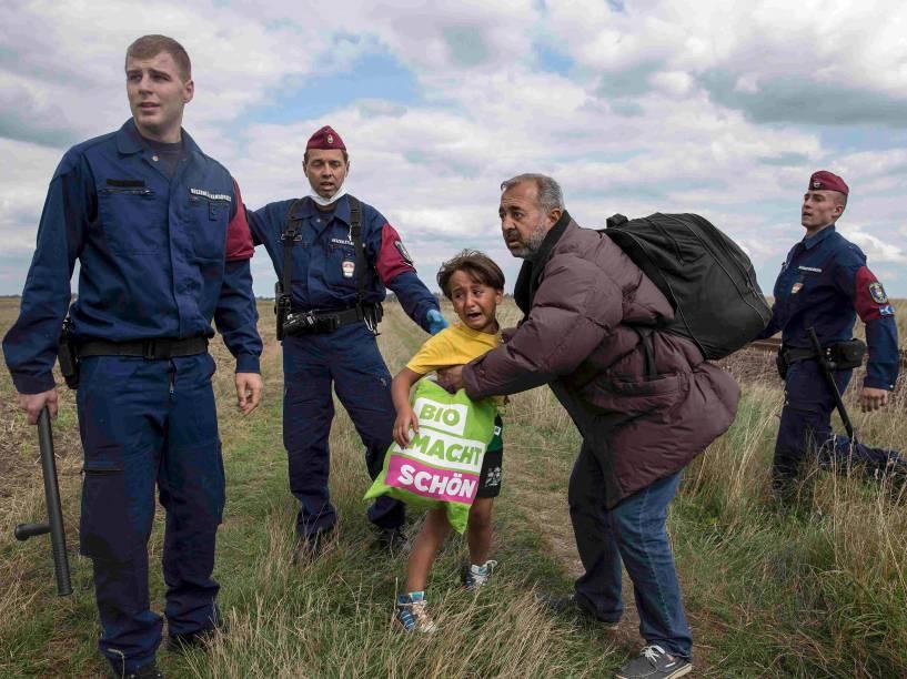 Criança chora ao ser detida pela polícia com o homem que a carregava enquanto tentavam atravessar a vila de Röszke, na Hungria - 08/09/2015