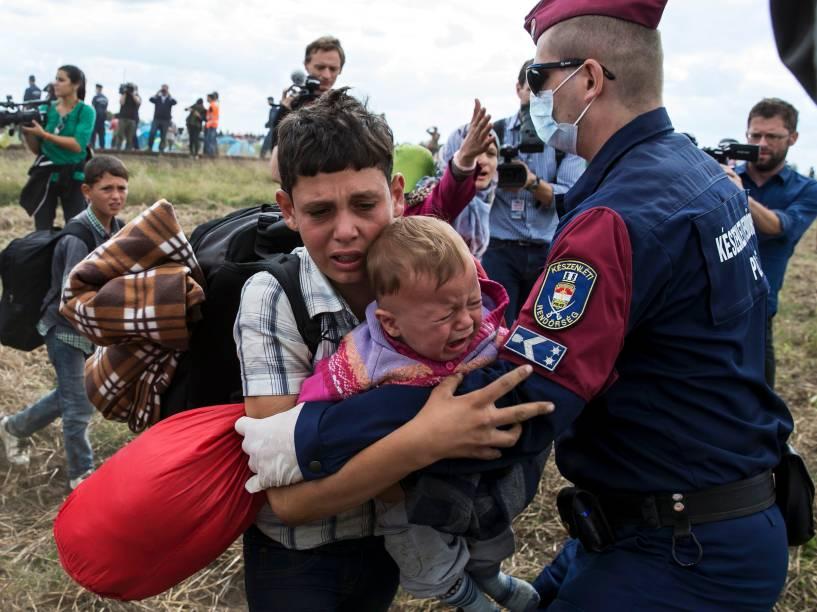 Policial tenta impedir a passagem de um menino refugiado com um bebê no colo na vila de Röszke, na Hungria - 08/09/2015