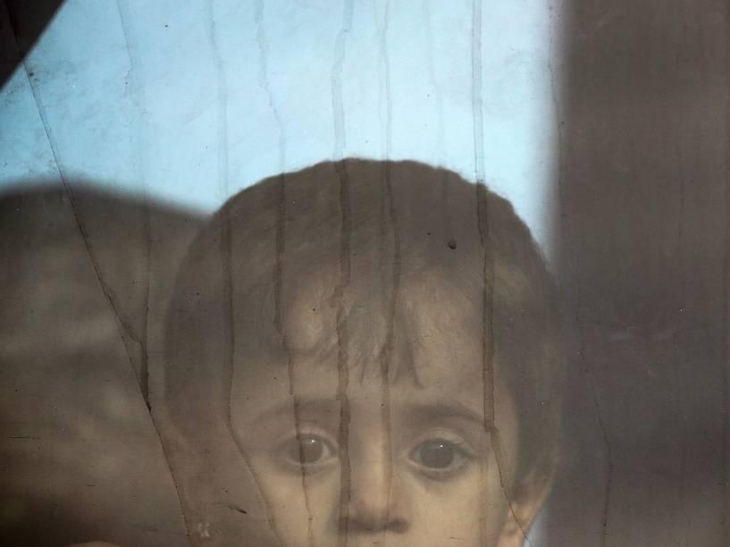 Menina síria olha da janela de um ônibus com refugiados na fronteira da Grécia com a Macedônia, perto da aldeia grega de Idomeni - 08/09/2015