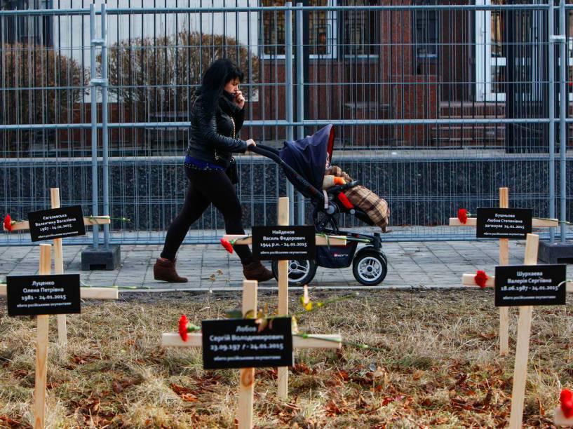 Mulher anda com carrinho de bebê em frente à cruzes postas no chão em homenagem aos mortos do bombardeio na cidade de Mariupol, Ucrânia, por combatentes pró-Rússia no último dia 24 de janeiro