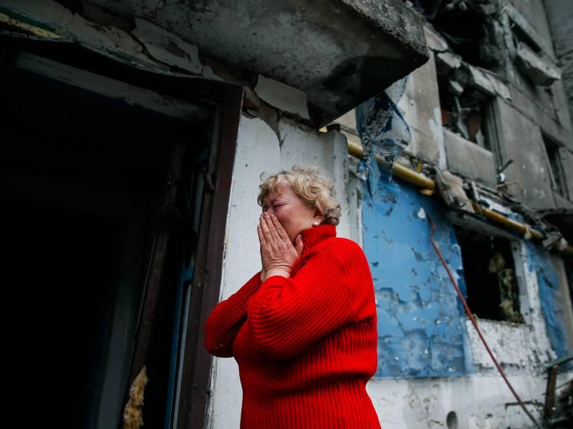 Mulher chora ao ver casas atingidas pelos bombardeios na cidade de Ienakiieve, na Ucrânia