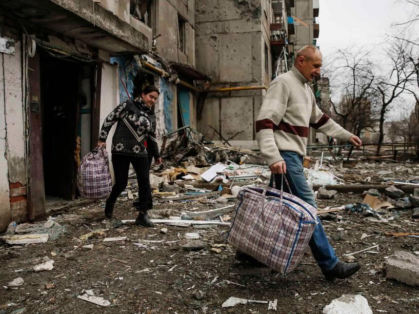 Moradores deixam suas casas após bombardeio na cidade de Ienakiieve, na Ucrânia