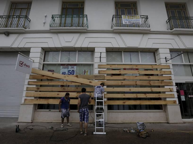 Homens colocam placas de madeira nas janelas de uma loja enquanto o furacão Patricia se aproxima de Puerto Vallarta, no México - 23/10/2015