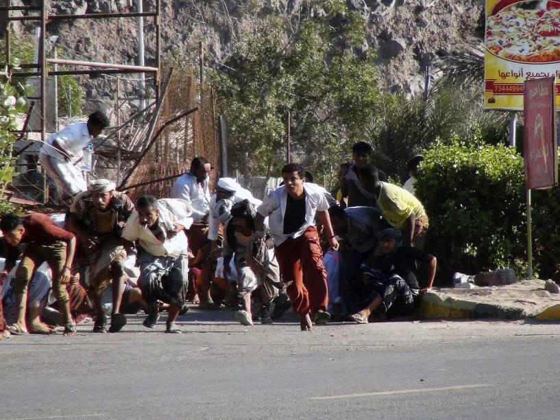 Pessoas procuram abrigo durante um tiroteio em uma base do exército na cidade portuária de Aden, no sul do Iêmen - 25/03/2015