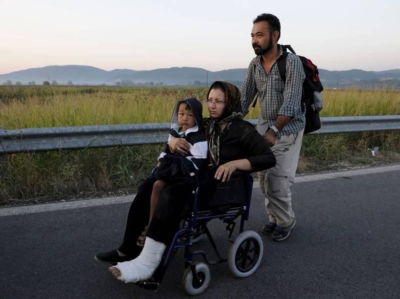 Mulher afegã com uma perna quebrada, segura seu filho enquanto seu marido empurra sua cadeira de rodas em uma estrada na da fronteira da Grécia com a Macedónia - 04/09/2015