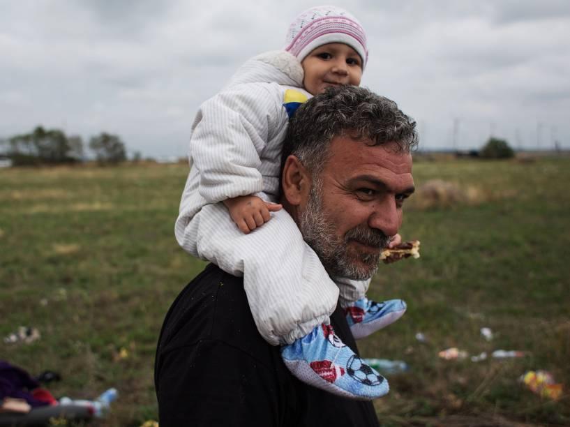 Refugiado carrega seu filho nos ombros enquanto caminha nos arredores da cidade austríaca de Nickelsdorf após cruzar a fronteira com a Hungria -  05/06/2015