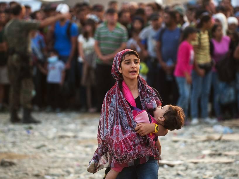 Mulher caminha com uma criança nos braços enquanto uma multidão de refugiados tenta embarcar em um trem indo para a Sérvia, na fronteira entre a Grécia e a Macedônia perto da cidade de Gevgelija - 05/09/2015