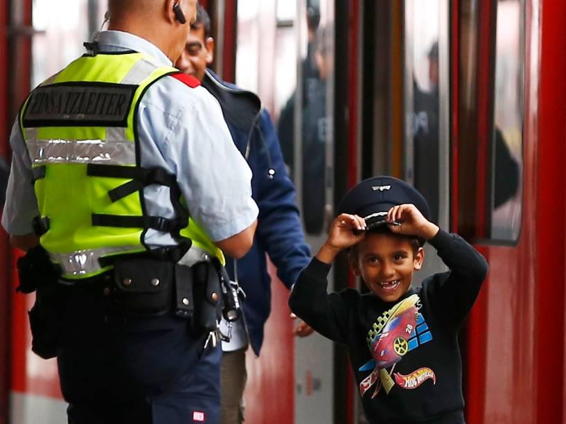 Menino refugiado brinca com o quepe de um oficial de segurança depois de desembarcar na principal estação de trem de Munique, na Alemanha - 05/09/2015