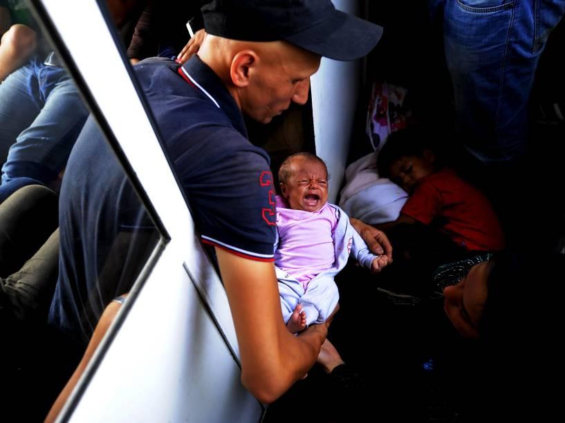 Imigrante sírio segura seu filho de apenas 30 dias em um trem superlotado enquanto viaja pela Macedônia. Milhares de imigrantes do Oriente Médio e da África, têm usado o país como rota para chegar à Europa Ocidental - 02/08/2015