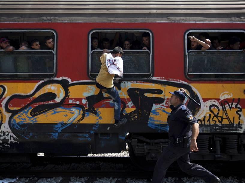 Policial tenta impedir o embarque de um imigrante em um trem na estação de Gevgelija, Macedônia - 15/08/2015
