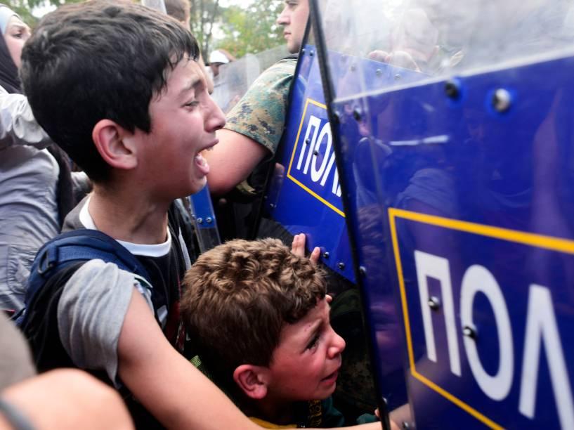 Meninos choram enquanto policiais macedônios bloqueiam um grupo de imigrantes que tentam atravessar uma área de fronteira ilegal com a Grécia - 21/08/2015