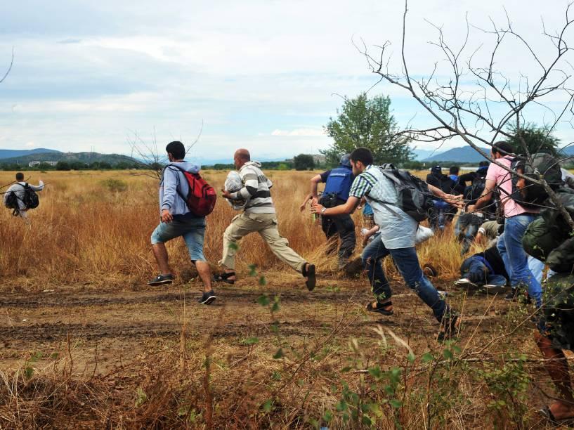 Imigrantes ultrapassam um bloqueio da polícia de fronteira da Macedônia perto da cidade de Idomeni, na fronteira com a Grécia - 22/08/2015