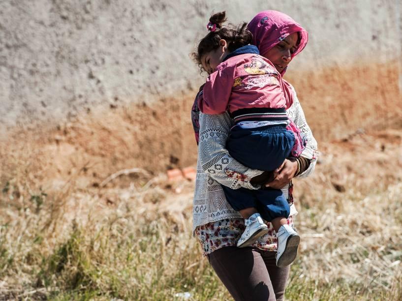 Mulher carrega uma criança enquanto se aproxima com outros imigrantes, da aldeia sérvia de Miratovac, viajando a pé desde a Macedônia - 24/08/2015