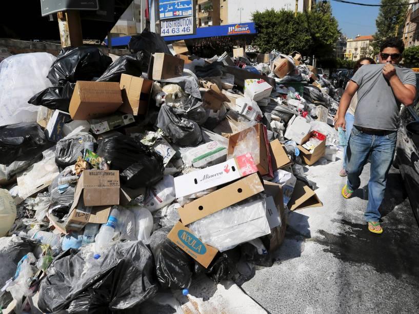 Homem cobre o nariz enquanto passa por uma pilha de lixo ao longo de uma rua em Beirute, no Líbano - 22/07/2015