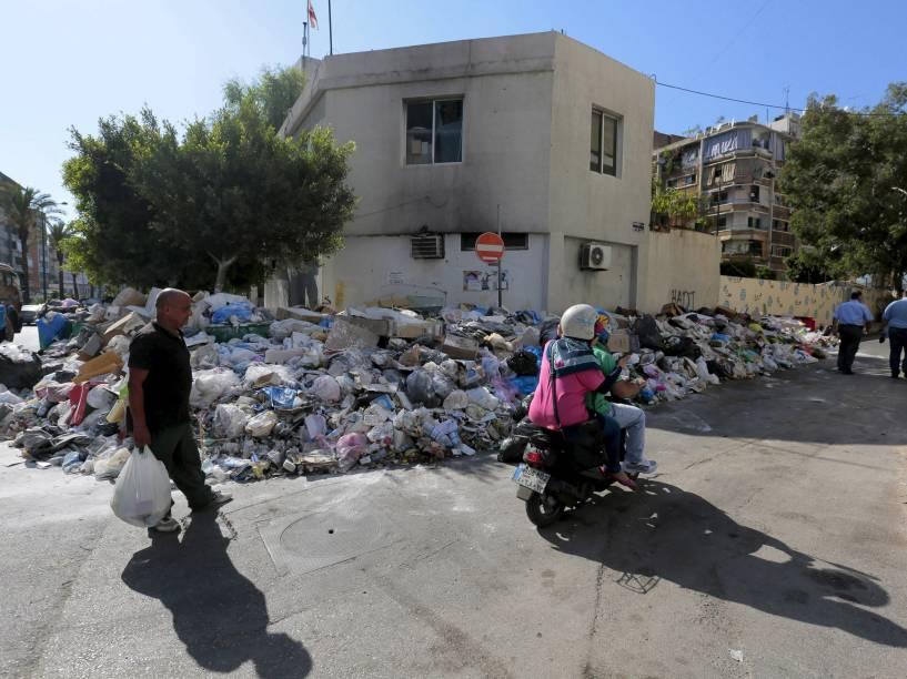 Pedestres caminham na rua para desviar do lixo acumulado na calçada em Beirute, no Líbano - 22/07/2015