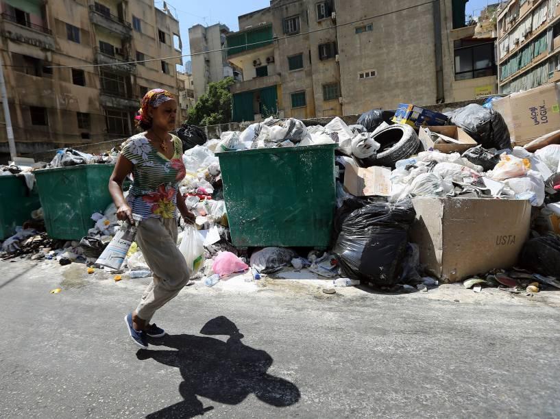 Mulher caminha através de uma montanha de lixo, polvilhada com pó de veneno para afastar ratos e insetos, em uma rua de Beirute, no Líbano - 23/07/2015