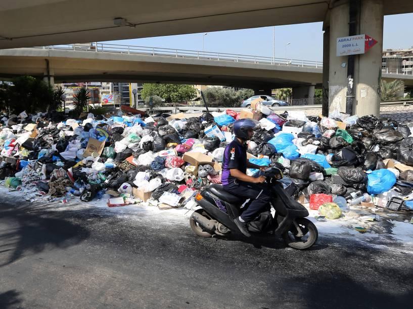 Motoqueiro passa diante de uma pilha de lixo acumulado em uma rua da cidade de Beirute, no Líbano - 23/07/2015