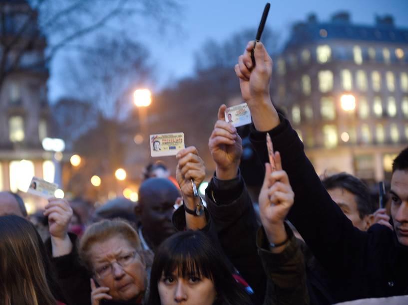 Jornalistas levantam seus cartões de imprensa e canetas, durante manifestação na Place de la Republique (Praça da República), em Paris - 07/01/2015