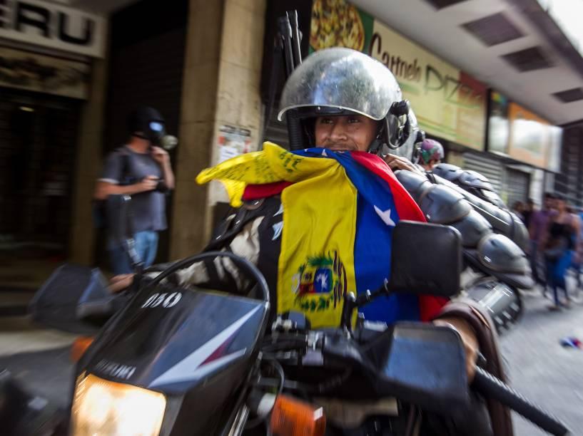 Membro da Polícia Nacional Bolivariana carrega uma bandeira da Venezuela durante manifestação pelo aniversário da prisão do líder da oposição Leopoldo López em Caracas - 18/02/2015
