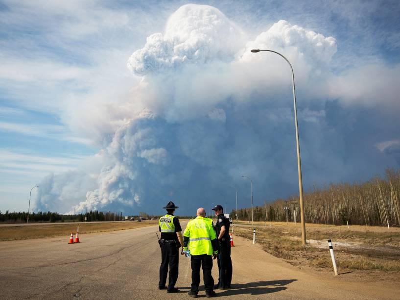 Policiais observam coluna de fumaça, provocada pelo incêndio florestal que atingiu a cidade de Fort McMurray, no Canadá. Mais de 80 mil pessoas foram evacuadas do local - 04/05/2016