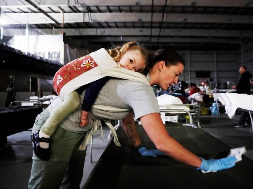 Voluntária limpa camas, com a filha em suas costas, para ajudar os habitantes da cidade de Fort McMurray, que perderam suas casas no incêndio florestal que atinge o local. Os evacuados estão sendo levados para a academia Bold Center, na província de Alberta, no Canadá - 05/05/2016
