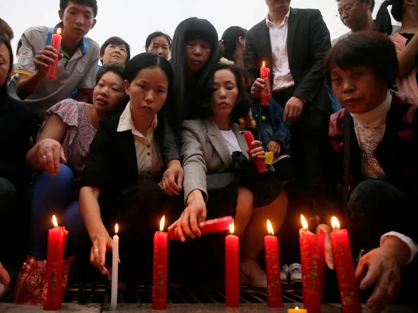 Pessoas acendem velas durante vigília em homenagem às vítimas do naufrágio no rio Yang Tsé