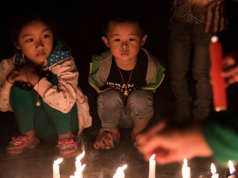 Crianças participam de vigília em homenagem às vítimas do naufrágio em Yang Tsé