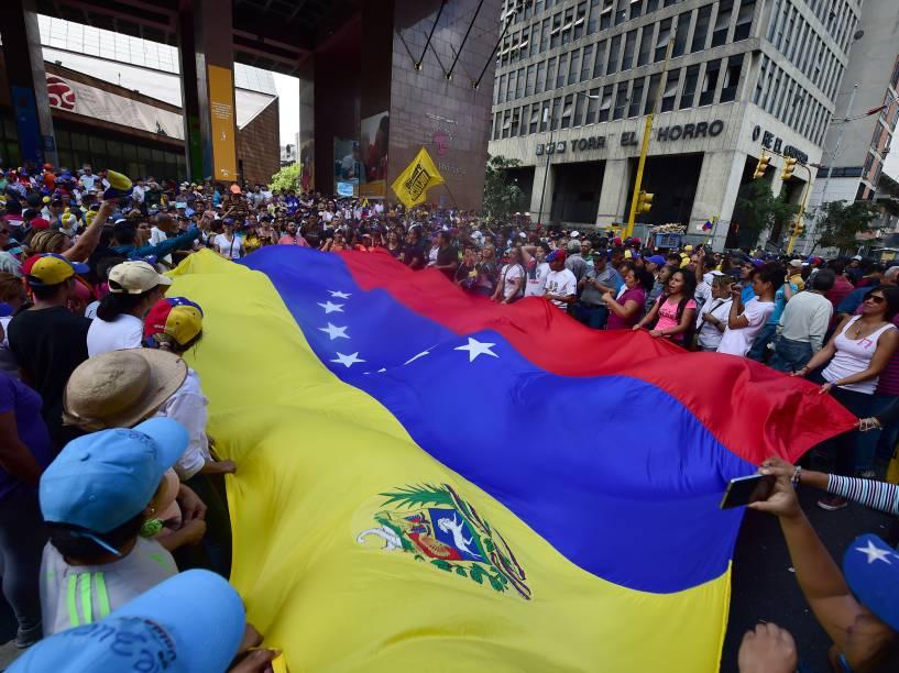 Manifestantes oposicionistas carregam uma bandeira da Venezuela em apoio aos deputados recém-eleitos em frente à Assembleia Nacional, em Caracas - 05/01/2016