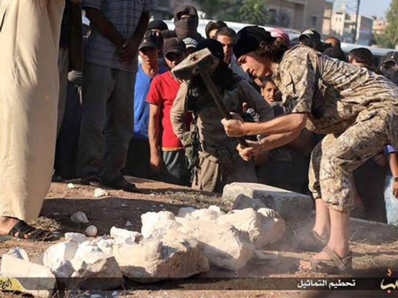 <p>Em Aleppo, um militante do Estado Islâmico destrói estátuas que seriam contrabandeadas da cidade histórica de Palmira, na Síria</p>