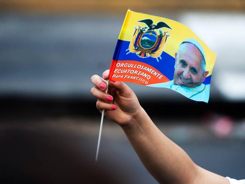 Fiel segura uma bandeira do Equador com a foto do Papa Francisco enquanto o líder da Igreja Católica desfila com papamóvel pelas ruas de Quito - 05/07/2015