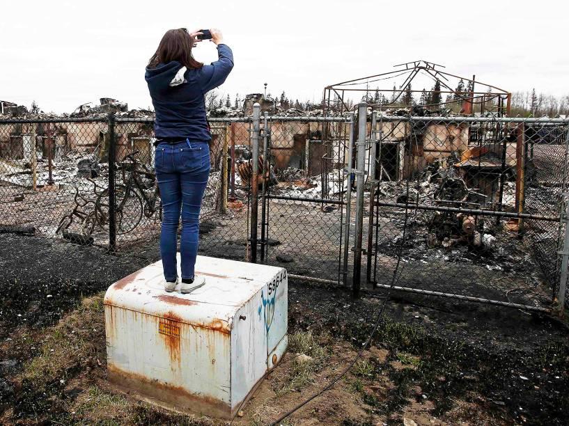 Mulher fotografa casas queimadas no bairro de Abasand, em Fort McMurray, no Canadá, após o grande incêndio que devastou a região nos últimos dias - 10/05/2016<br><br>