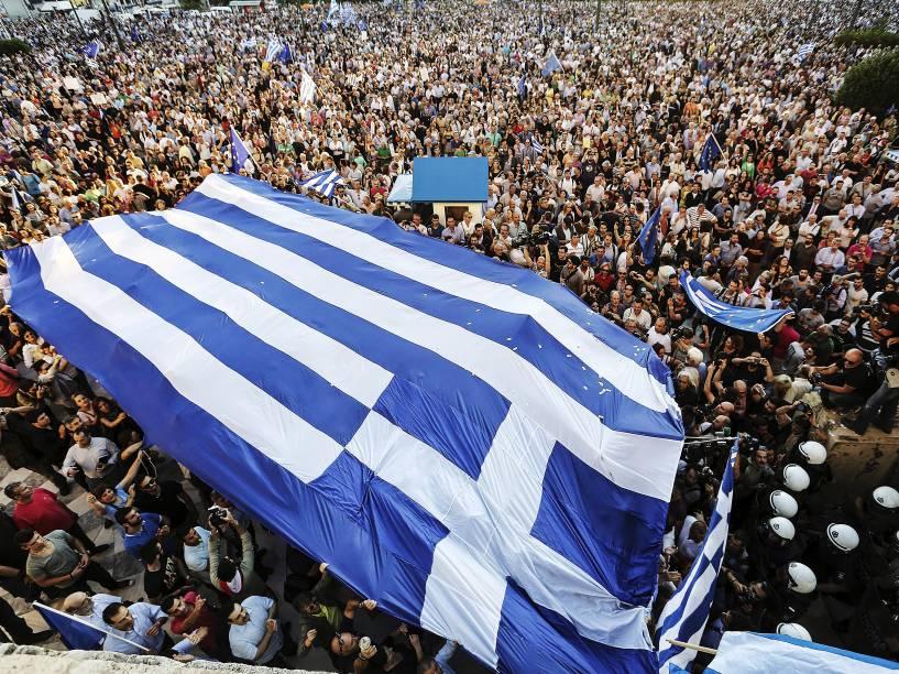 Manifestantes carregam uma bandeira grega durante um comício em frente ao edifício do parlamento em Atenas pedindo ao governo para fechar um acordo com seus credores internacionais e garantir o futuro da Grécia na zona do euro - 22/06/2015