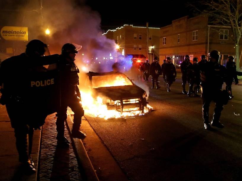 Policiais passam ao lado de carro incendiado em meio a protestos em Ferguson, Missouri, pela decisão do júri de não indiciar um policial pela morte de Michael Brown, um jovem negro desarmado - 24/11/2014