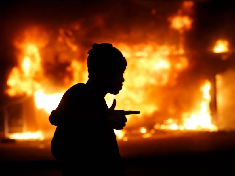 Homem passa por um edifício incendiado em meio a protestos em Ferguson, Missouri, após decisão do júri de não indiciar um policial pela morte de Michael Brown, um jovem negro desarmado - 24/11/2014