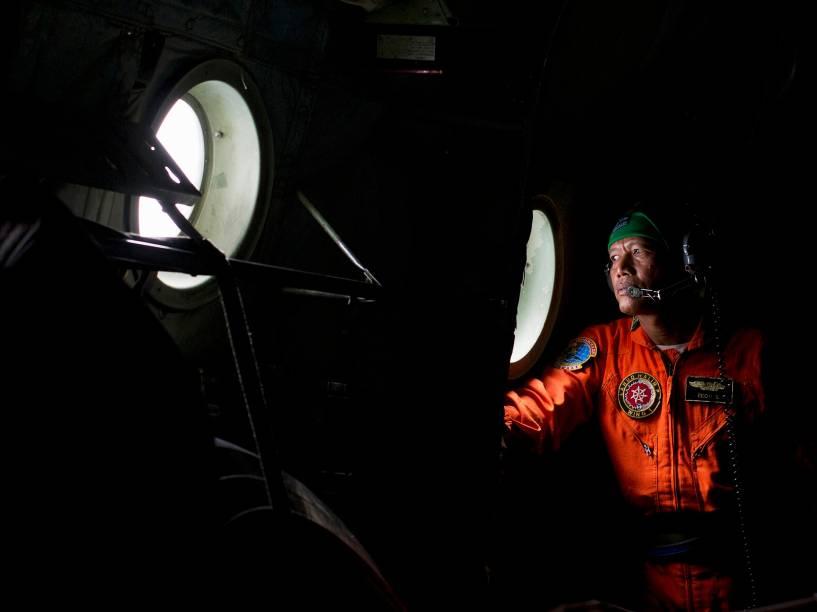Membro de uma equipe de resgate observa da janela a região da ilha de Belitung, na Indonésia, durante operação que tenta localizar aeronave da AirAsia - 29/12/2014
