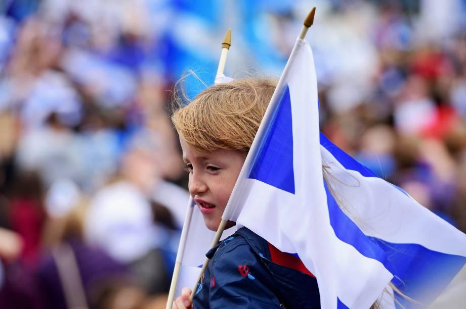 Garoto segura bandeiras pró-independência em marcha até a BBC Scotland em Glasgow, Escócia - 14/09/2014