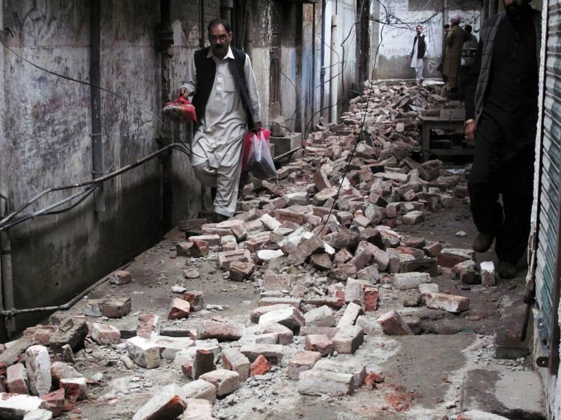 Homem caminha entre os escombros de uma casa danificada por um terremoto em Mingora, Swat, no Paquistão - 26/10/2015