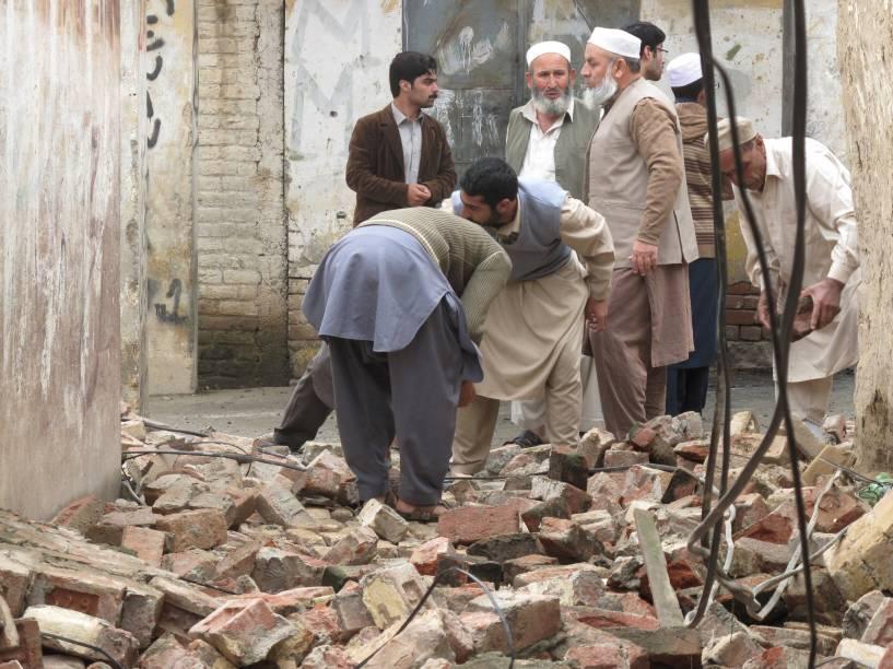 Moradores se reúnem para abrir um caminho através da remoção de escombros de uma casa depois que ela foi danificada por um terremoto em Mingora, Swat, Paquistão