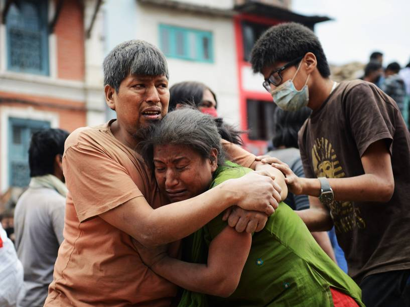 Familiares se abraçam na Praça Durbar em Katmandu, Patrimônio Mundial da Unesco, que foi severamente danificada pelo terremoto