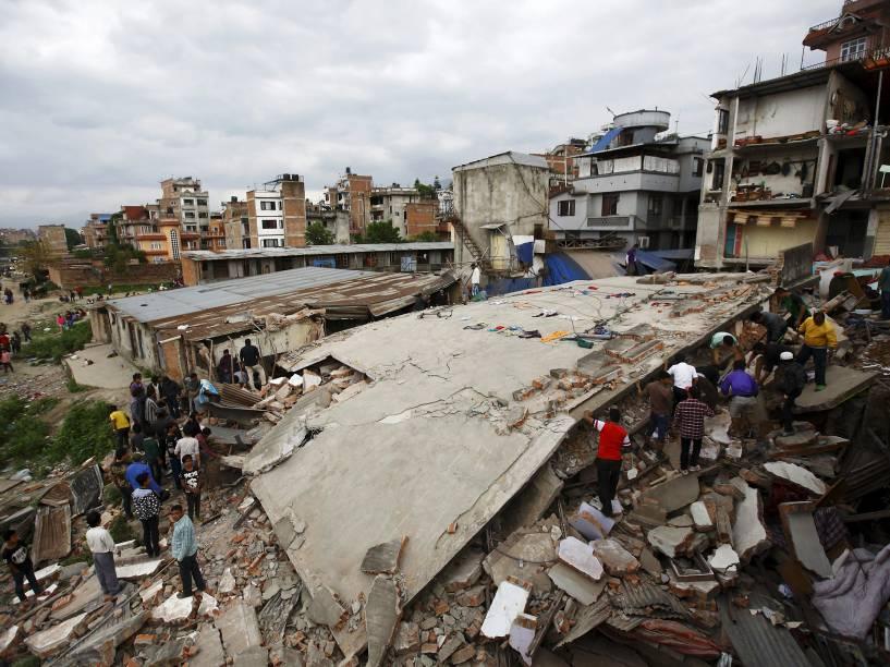 Pessoas se reúnem perto de uma casa que desabou após o terremoto de magnitude 7,8 em Katmandu, Nepal - 25/04/2015