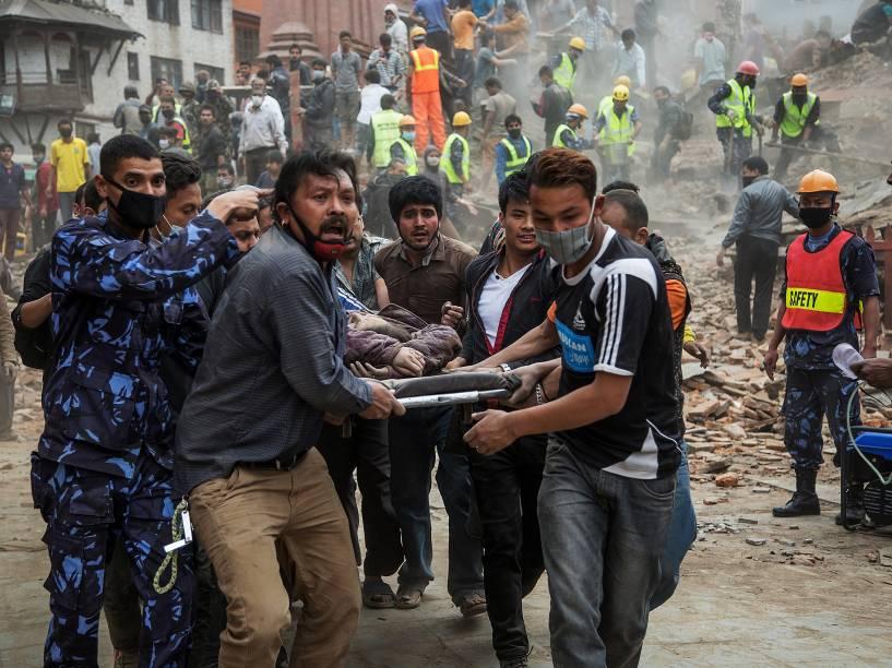 Equipes de resgate carregam uma vítima após o desabamento da torre Dharara, em Katmandu, Nepal - 25/04/2015