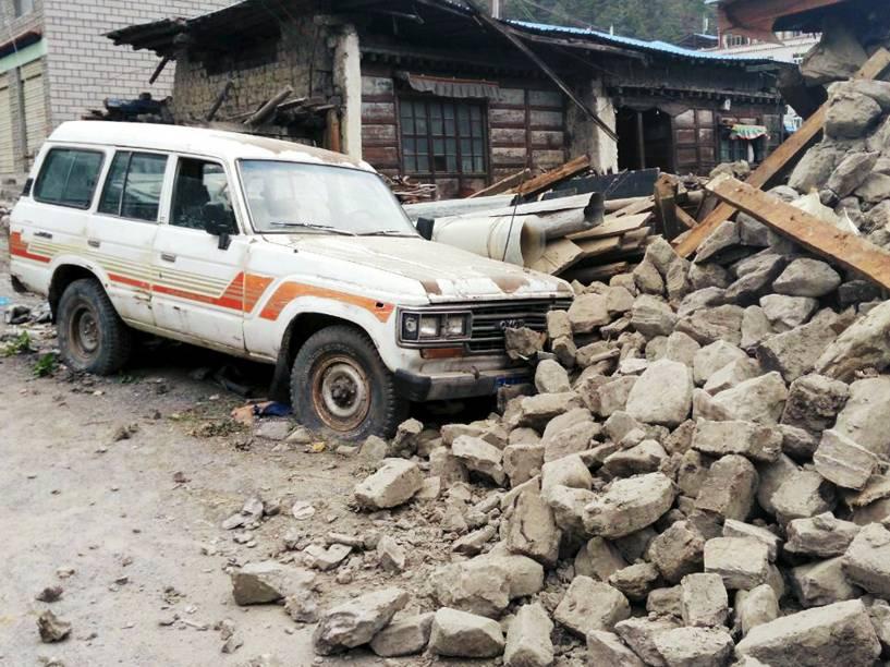 Carro junto aos escombros de uma casa, após o terremoto de magnitude 7,8 que atingiu o Nepal, próximo à prefeitura de Xigaze, na região autônoma do Tibet, China - 25/04/2015