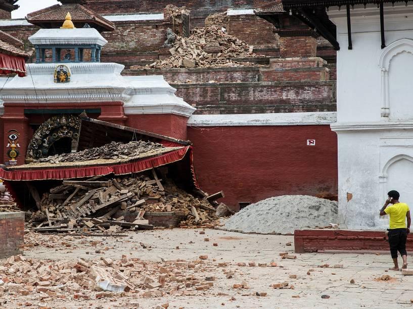 Homem fala ao celular em frente a um templo que desabou após o terremoto de magnitude 7,8 no centro da cidade Katmandu, Nepal